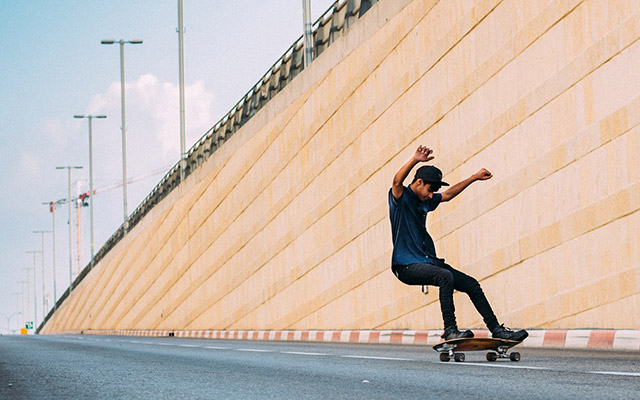 A teenager skateboards on a highway ramp