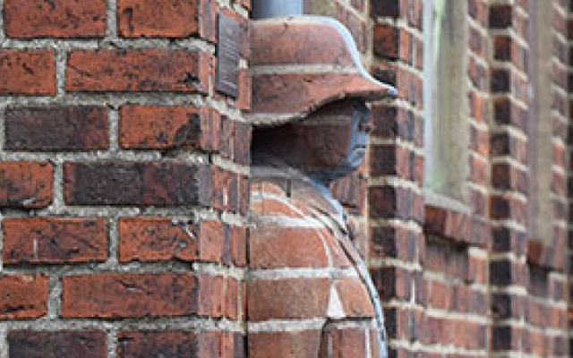 Statue of a man in a brick wall