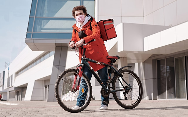 A bicycle delivery worker poses in front of a building